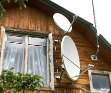Любительское фото небольшого дачного домика, который оснащен антеннами для приема спутникового сигнала