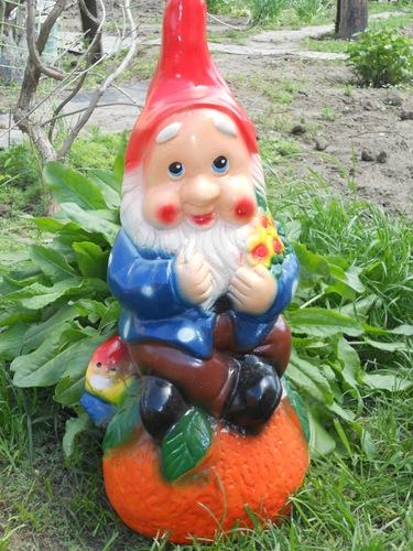 Демонстрируется гипсовый гном, сидящий на фрукте.