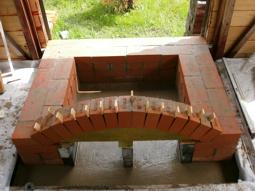 Между кирпичами арки вставляются клинышки для обеспечения одинаковой ширины шва