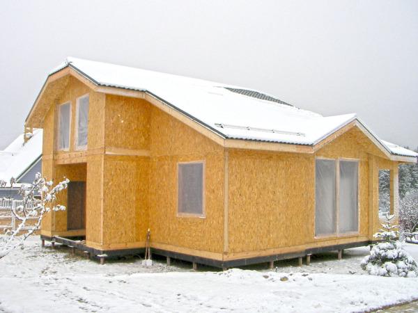 На фото - дом из сип-панелей. Качественное утепление снижает потребность в тепле вдвое.