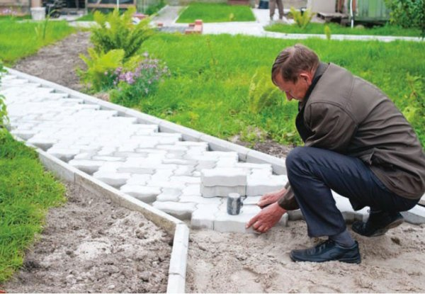 На фото - укладка тротуарной плитки на даче с применением простых и доступных инструментов