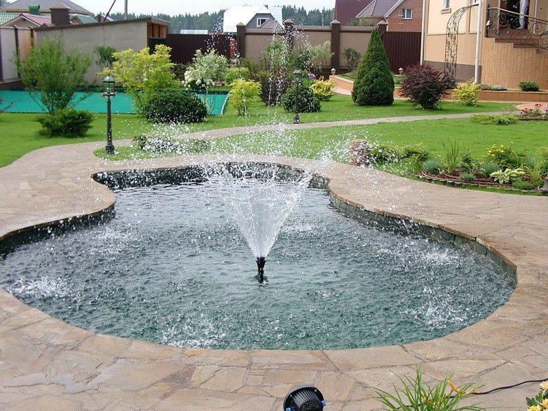 Площадка вокруг фонтана вымощена диким камнем.