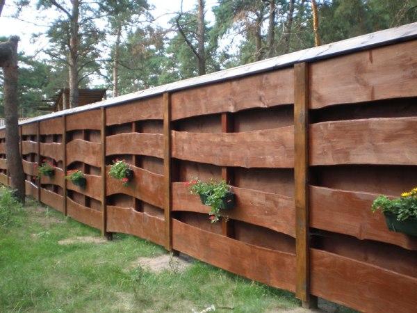 Видно, что защита верхней части деревянной ограды козырьком целесообразна
