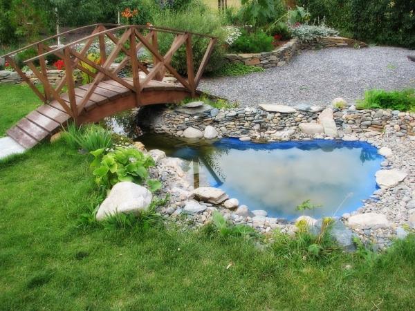 Вместо круглой емкости отрыт и забетонирован продолговатый пруд, через который перекинут изящный мостик.