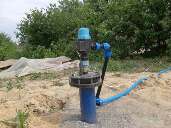 Внешний вид водоносной скважины с оголовком и установленным насосным оборудованием