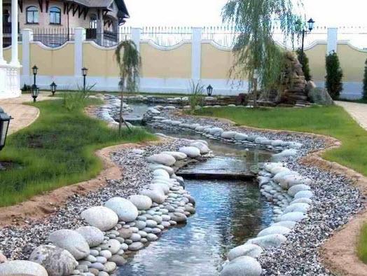 Здесь дизайнер пошел еще дальше: через участок течет настоящая река. Ее исток - фонтан на небольшом пригорке; он связан с расположенным ниже по течению насосом уложенной в грунт металлопластиковой трубой.